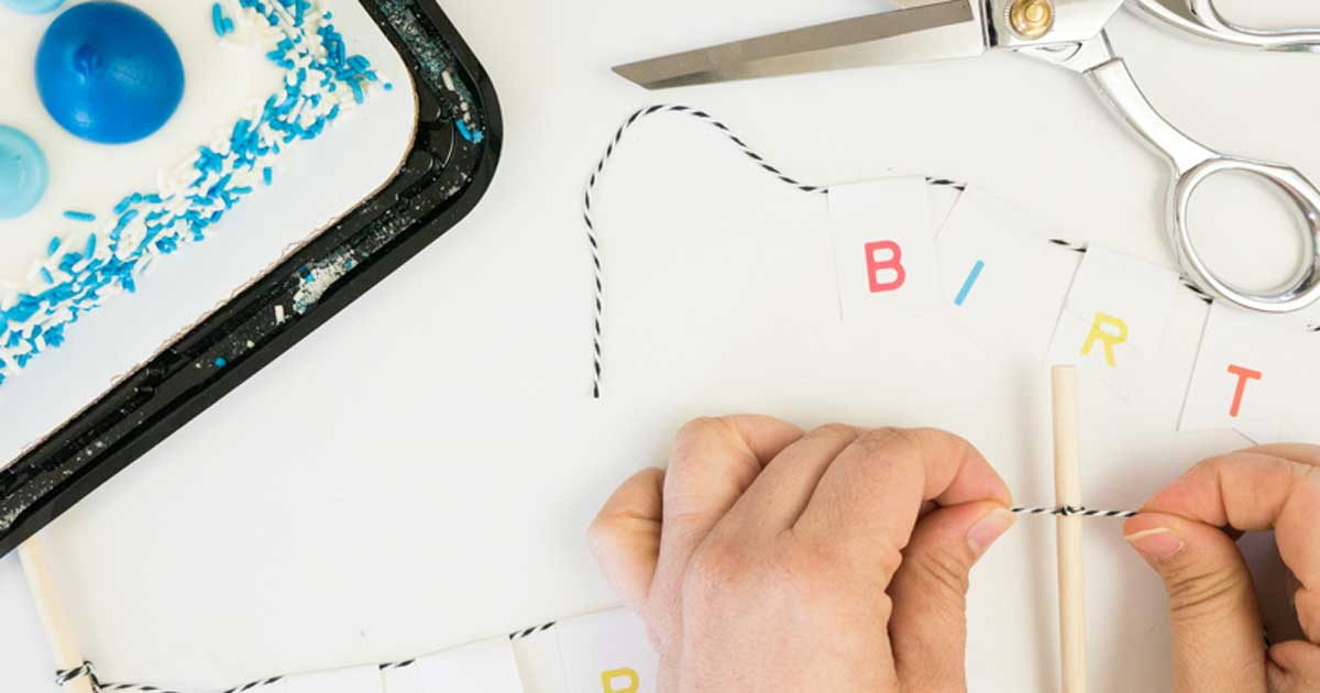 DIY birthday banner tutorial: Tie the label string onto the rods