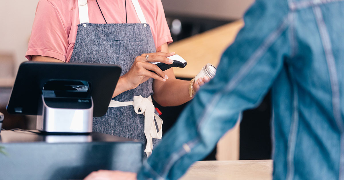 Small business owner using barcode scanner to check out customer