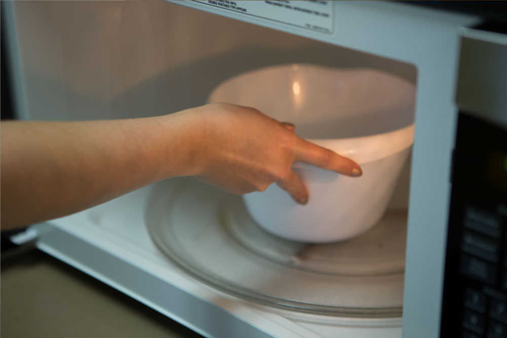 Placing bowl in the microwave.