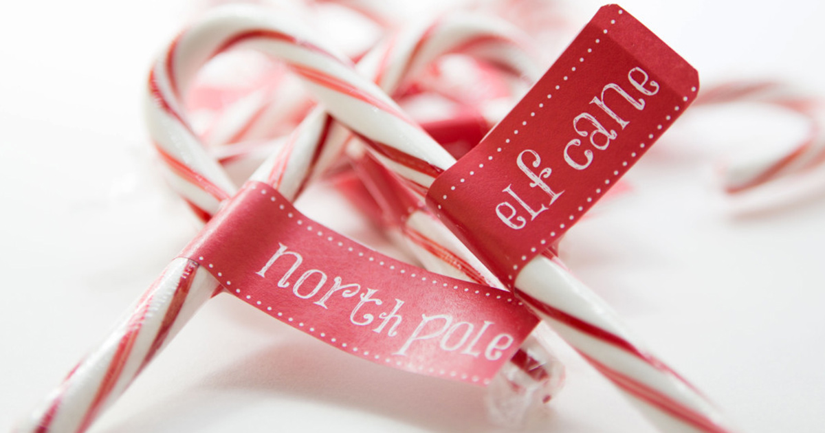 Christmas party decor with DIY candy cane printables: North Pole and Elf Cane labels wrapped around candy canes