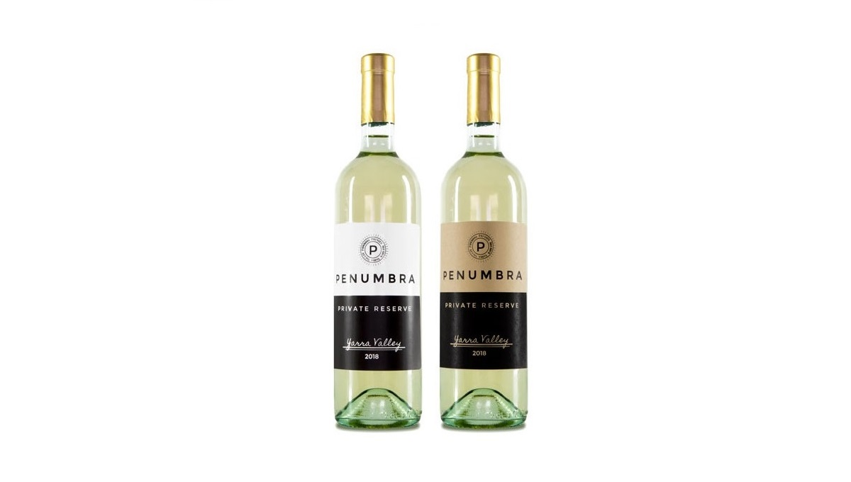 Two wine bottles. One featuring a white matte label, the other featuring a brown kraft label