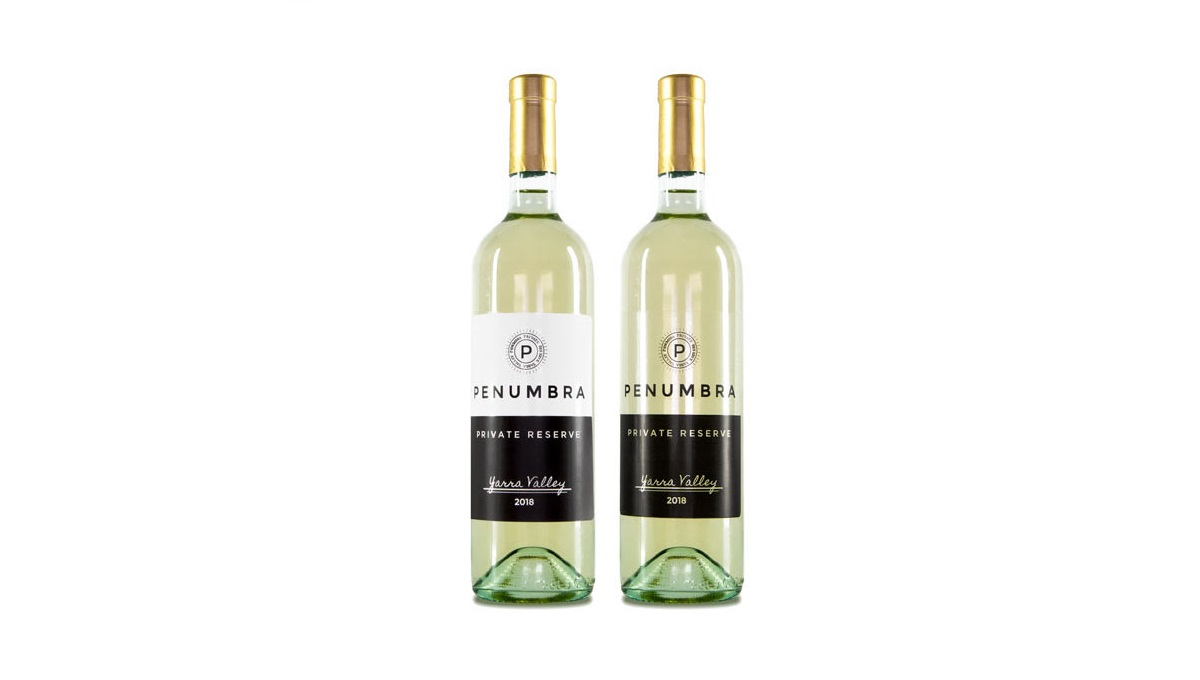 Two wine bottles. One featuring a white matte label, the other featuring a clear gloss label