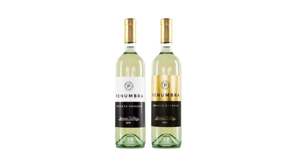 Two wine bottles. One featuring a white matte label, the other featuring a metallic gold foil label