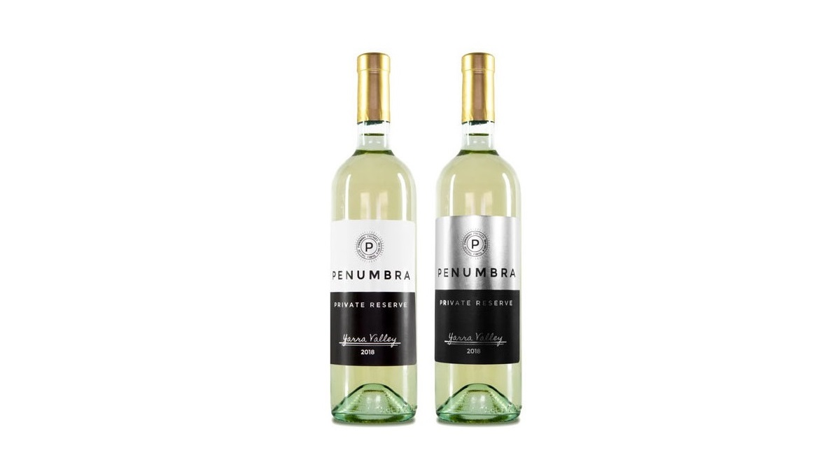 Two wine bottles. One featuring a white matte label, the other featuring a metallic silver foil label